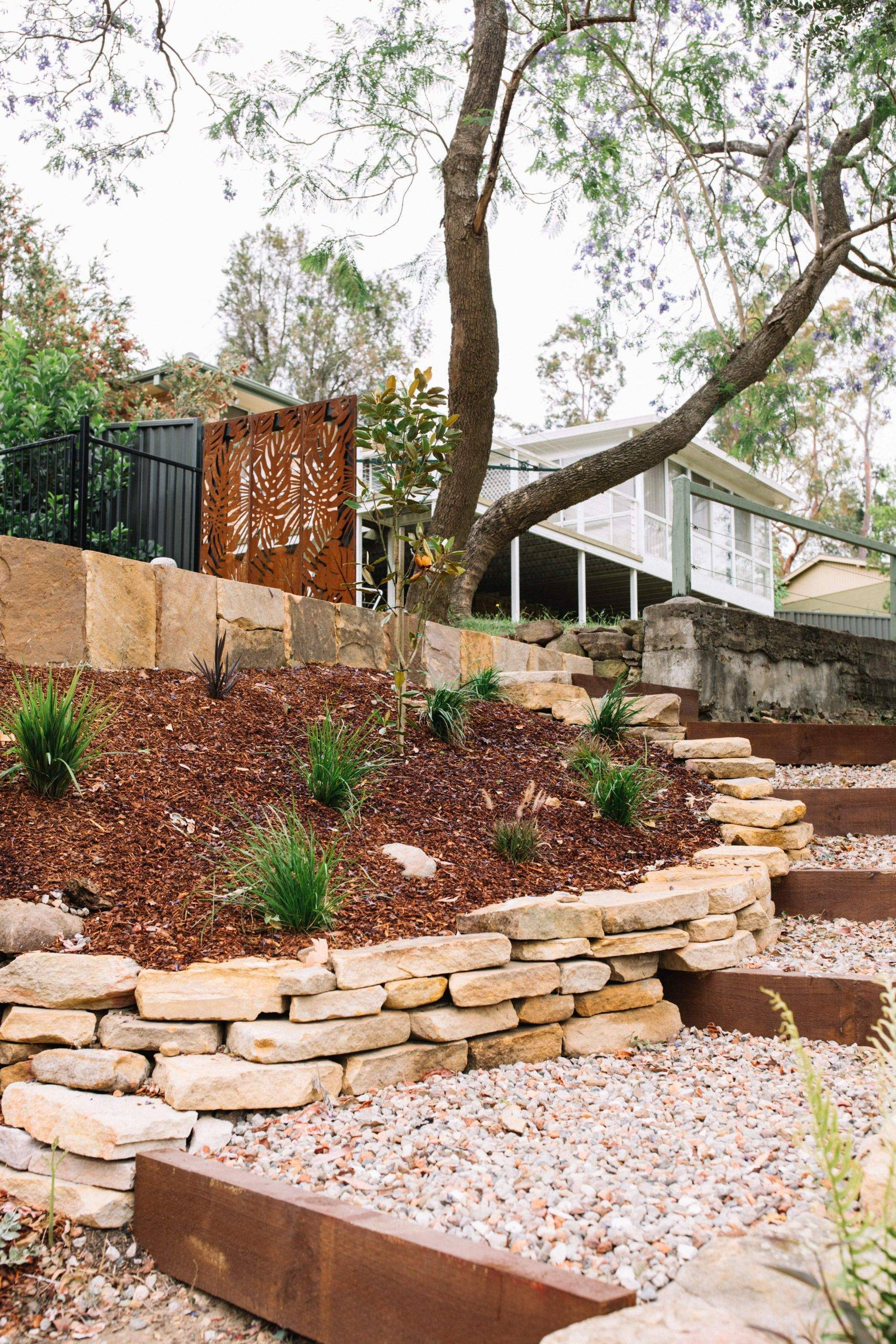 Sloping block landscape design retaining walls