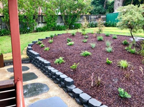 block retaining wall construction surrounding garden bed
